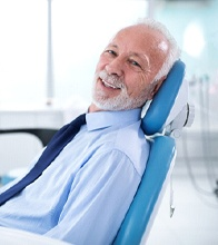 Older man smiling in dental chair looking at camera
