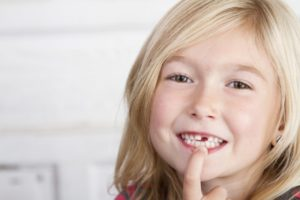 little girl pointing at missing tooth