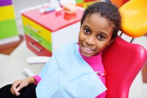 a young girl sitting in the dentist chair smiling