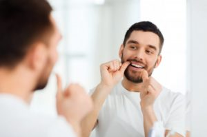 man flossing to maintain oral hygiene during COVID-19