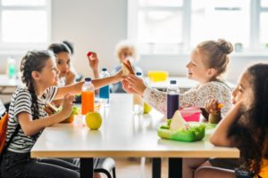 four girls eating school lunches at cafeteria table