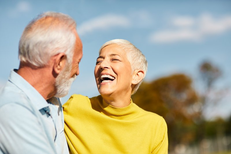 an older couple laughing and smiling while enjoying the outdoors