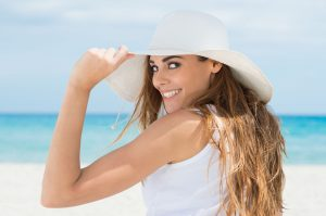 woman on the beach with a bright smile thanks to summer oral health tips in Blaine
